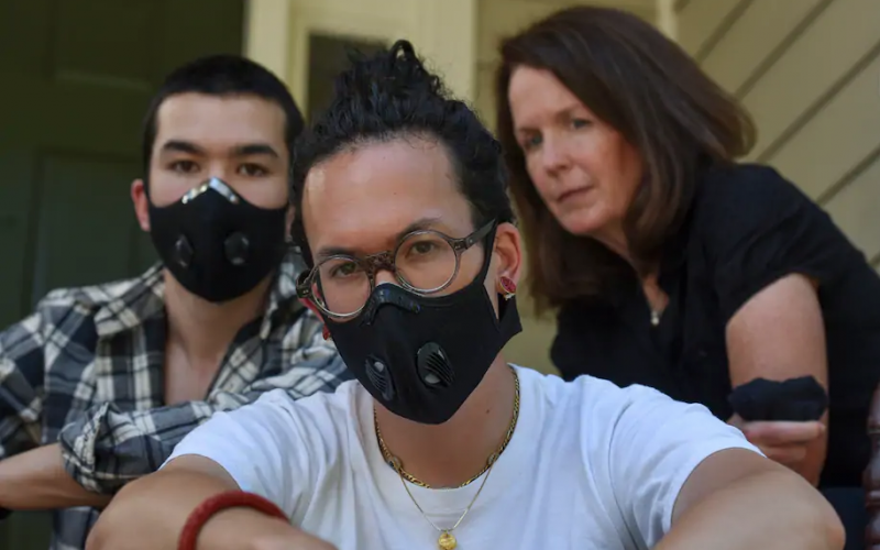 Charlie Mai, 24, center, and Henry Mai, 22, left, with their mother, Mary Byrne, at their home in Arlington, Va. Their father threatened to leave during an argument over the George Floyd protests. (Jahi Chikwendiu/The Washington Post)