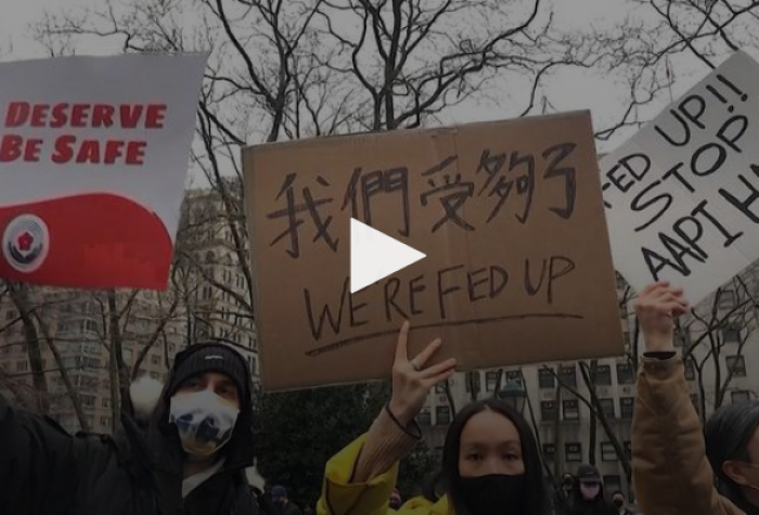 Still from Democracy Now! broadcast showing demonstrators holding signs reading: We deserve to be safe; We're fed up; Stop AAPI Hate